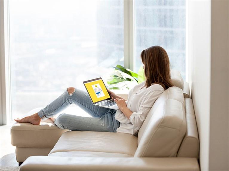 Frau auf Couch mit Laptop