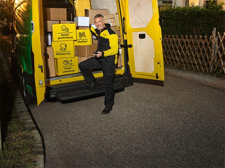 Zusteller vor offenem Lieferwagen mit vielen Paketen