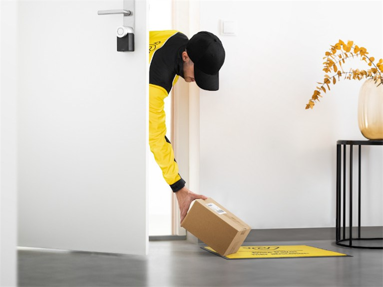 Delivery person placing a parcel inside a home.