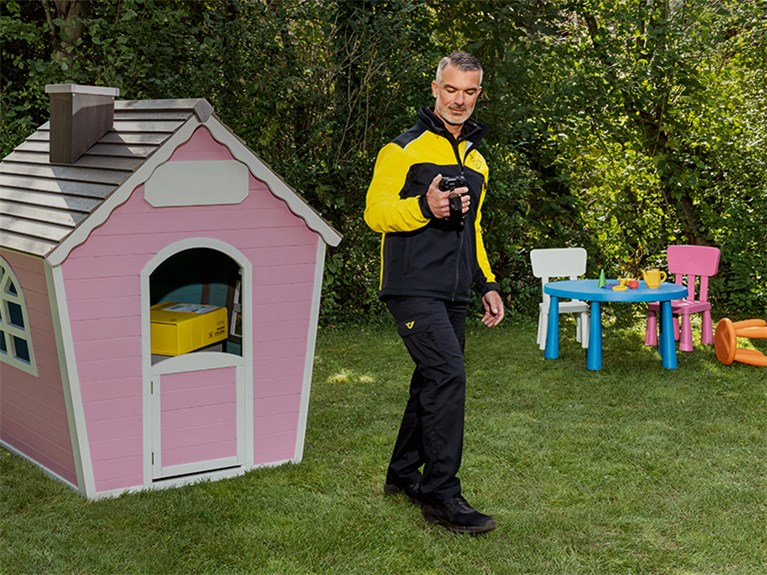 Delivery person with parcels in front of a children's playhouse